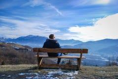 Jeune homme s'asseyant sur un banc Photographie stock