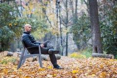 Jeune homme s'asseyant sur un banc en stationnement photographie stock libre de droits