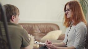 Jeune homme s'asseyant sur un berceau dans le bureau d'un psychologue, lui indiquant au sujet de ses problèmes Belle femelle clips vidéos
