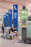 Jeune homme s'asseyant sur un chariot, aéroport international capital de Pékin Photo stock