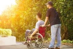 Jeune homme s'asseyant sur un fauteuil roulant avec son frère Image stock
