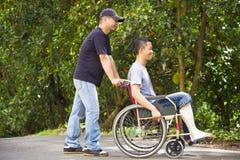Jeune homme s'asseyant sur un fauteuil roulant avec son frère Images stock