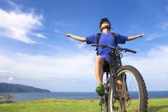 Jeune homme s'asseyant sur un vélo de montagne et des bras ouverts à la détente Image stock