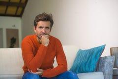 Jeune homme 30s attirant et heureux souriant séance décontractée et confortable au divan de sofa de salon dans son acclamation mo photo libre de droits