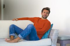 Jeune homme 30s attirant et heureux souriant séance décontractée et confortable au divan de sofa de salon dans son acclamation mo images libres de droits