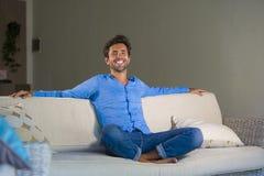 Jeune homme 30s attirant et heureux souriant séance décontractée et confortable au divan de sofa de salon dans son acclamation mo photographie stock