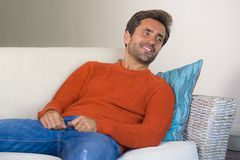 Jeune homme 30s attirant et heureux souriant séance décontractée et confortable au divan de sofa de salon dans son acclamation mo photos stock