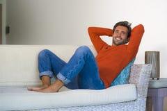 Jeune homme 30s attirant et heureux souriant séance décontractée et confortable au divan de sofa de salon dans son acclamation mo photo stock