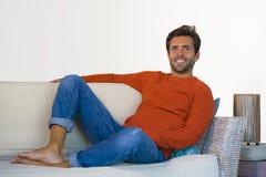Jeune homme 30s attirant et heureux souriant séance décontractée et confortable au divan de sofa de salon dans son acclamation mo image stock