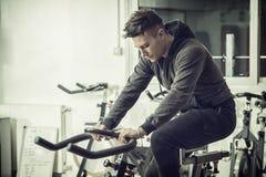 Jeune homme s'exerçant dans le gymnase : rotation sur le vélo stationnaire Photos stock