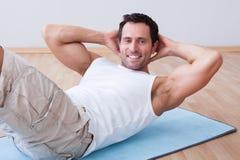 Jeune homme s'exerçant sur le couvre-tapis d'exercice Photographie stock