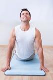 Jeune homme s'exerçant sur le couvre-tapis d'exercice Images stock