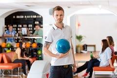 Jeune homme sûr avec la boule de bowling dans le club Photo libre de droits