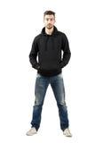 Jeune homme sûr dans le capot avec des mains dans la poche regardant l'appareil-photo Image stock
