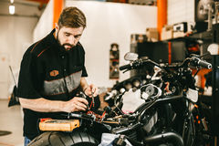 Jeune homme sûr réparant la moto dans l'atelier de réparations - réparation de l'électronique Photo libre de droits