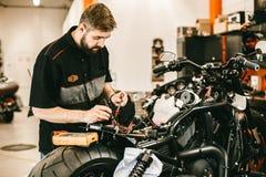 Jeune homme sûr réparant la moto dans l'atelier de réparations - réparation de l'électronique Photos stock
