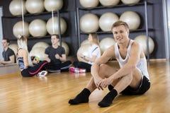 Jeune homme sûr s'asseyant sur le plancher au gymnase Images stock