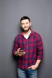 Jeune homme sûr tenant le téléphone intelligent et le regardant tout en se tenant sur le fond gris Photo stock