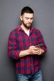 Jeune homme sûr tenant le téléphone intelligent et le regardant tout en se tenant sur le fond gris Photos libres de droits
