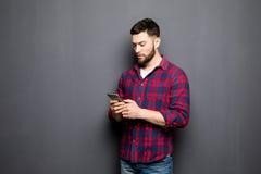 Jeune homme sûr tenant le téléphone intelligent et le regardant tout en se tenant sur le fond gris Photographie stock