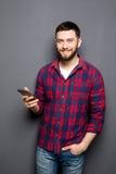Jeune homme sûr tenant le téléphone intelligent et regardant l'appareil-photo tout en se tenant sur le fond gris Photo stock