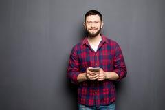 Jeune homme sûr tenant le téléphone intelligent et regardant l'appareil-photo tout en se tenant sur le fond gris Photos libres de droits