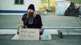 Jeune homme sans abri barbu avec le carton se reposant près du caddie et de l'alcool de boissons au jour froid Photos stock