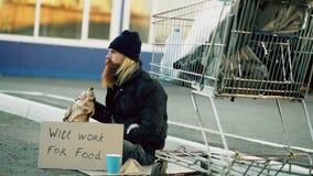 Jeune homme sans abri barbu avec le carton se reposant près du caddie et de l'alcool de boissons au jour froid Images stock