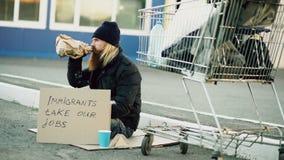 Jeune homme sans abri barbu avec le carton se reposant près du caddie et de l'alcool de boissons au jour froid Crise d'immigrés d Image stock