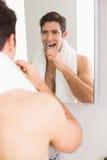Jeune homme sans chemise avec les dents de brossage de réflexion Image libre de droits