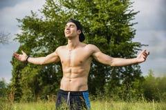 Jeune homme sans chemise célébrant la nature à Photographie stock