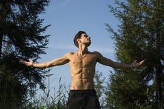 Jeune homme sans chemise célébrant la nature Image stock