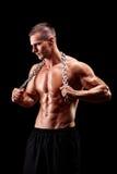 Jeune homme sans chemise tenant une chaîne autour de son cou Images stock