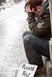 Jeune homme sans foyer priant dans la rue Photographie stock