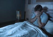 Jeune homme sans sommeil triste et déprimé se trouvant sur se sentir de lit à la maison inquiété et réfléchi de chambre à coucher photographie stock libre de droits