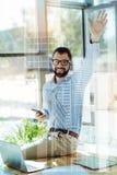 Jeune homme satisfaisant jugeant la main haut et le sourire Photos stock