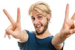 Jeune homme satisfait faisant le signe de victoire Photos libres de droits