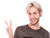 Jeune homme satisfait faisant le signe de victoire Image stock