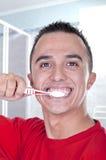 Jeune homme se brossant les dents Photo stock