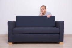 Jeune homme se cachant derrière un sofa et montrant shhh le signe Images stock
