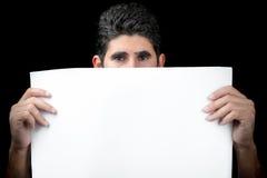 Jeune homme se cachant derrière une bannière blanche Photographie stock