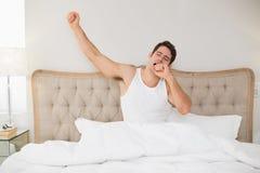 Jeune homme se réveillant dans le lit et étirant des bras Photo stock