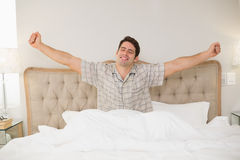 Jeune homme se réveillant dans le lit et étirant ses bras Image stock