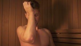 Jeune homme se relaxant dans le sauna et restant en bonne santé banque de vidéos
