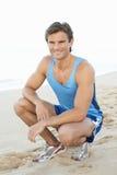 Jeune homme se reposant après exercice sur la plage images stock