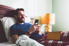 Jeune homme se situant dans le lit avec un bookand un smartphone Image libre de droits