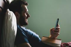 Jeune homme se situant dans le lit avec un livre et un smartphone Photo stock