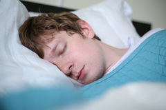 Jeune homme se situant dans le lit - plan rapproché Images stock