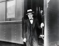 Jeune homme se tenant à l'entrée d'un train (toutes les personnes représentées ne sont pas plus long vivantes et aucun domaine n' photographie stock