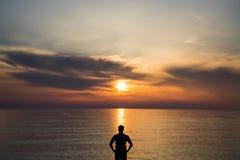 Jeune homme se tenant à la plage devant la vue étonnante de mer au coucher du soleil ou au lever de soleil et pensant à son aveni Image libre de droits